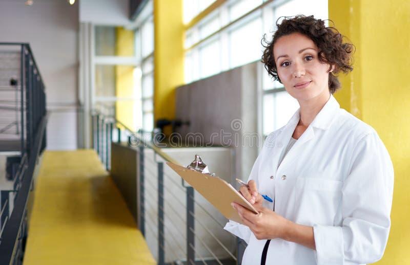 Stående av en kvinnlig doktor som rymmer hennes tålmodiga diagram i ljust modernt sjukhus arkivbilder