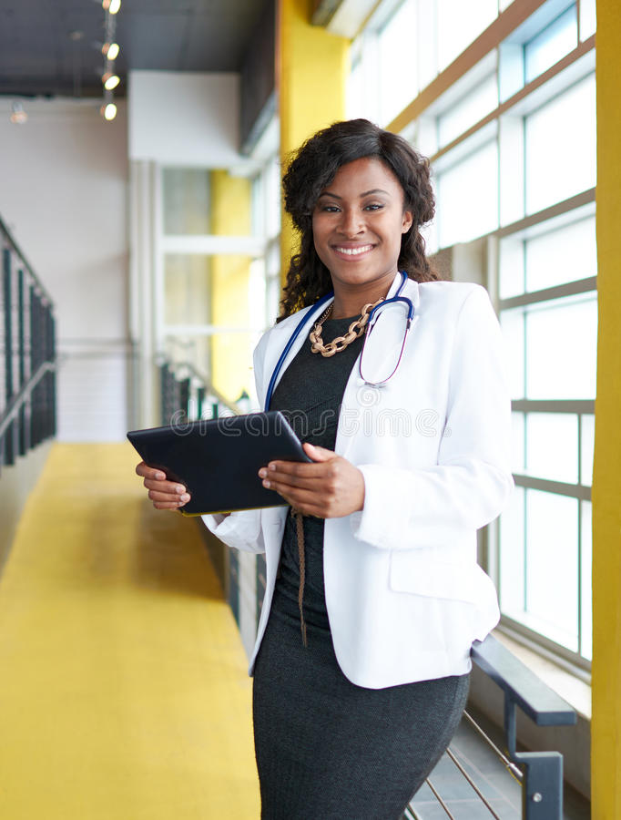 Stående av en kvinnlig doktor som rymmer hennes tålmodiga diagram på den digitala minnestavlan i ljust modernt sjukhus arkivbild