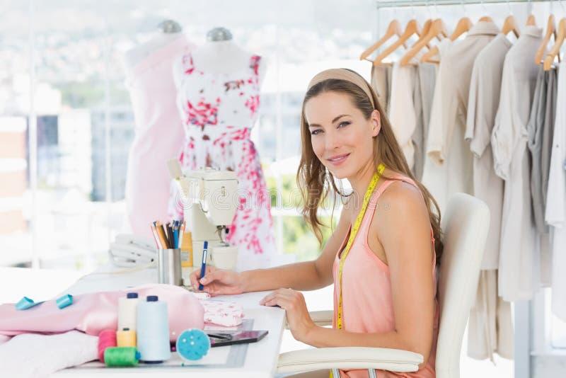 Stående av en kvinnlig modeformgivare som arbetar på hennes designer arkivfoton