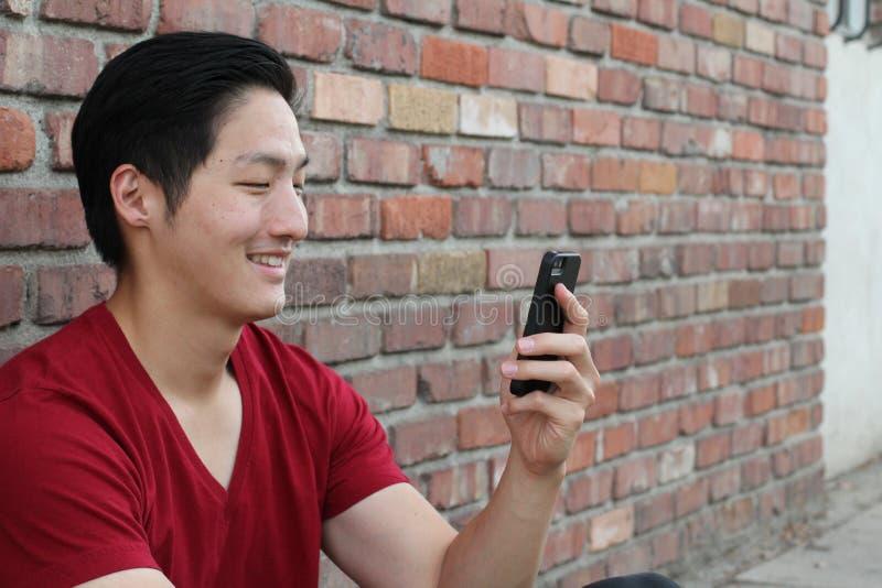 Stående av en le asiatisk grabb som utanför smsar på mobiltelefonen royaltyfria foton