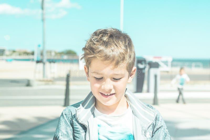 Stående av en le blond pojke som ner ser på jordningen royaltyfri fotografi
