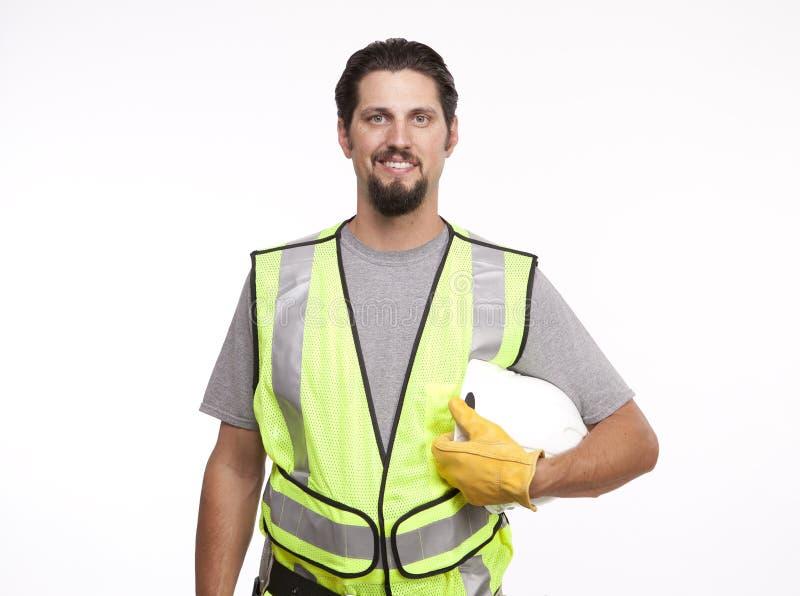 Stående av en le byggnadsarbetare med en hardhat royaltyfri bild
