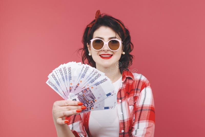 Stående av en le flicka som rymmer gruppen av pengarsedlar och ser mobiltelefonen som isoleras över rosa färger royaltyfria foton