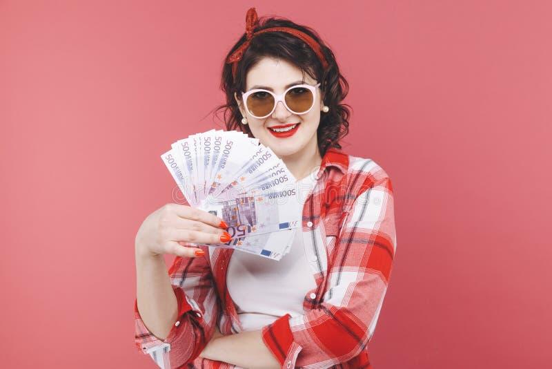 Stående av en le flicka som rymmer gruppen av pengarsedlar och ser mobiltelefonen som isoleras över rosa färger arkivfoton