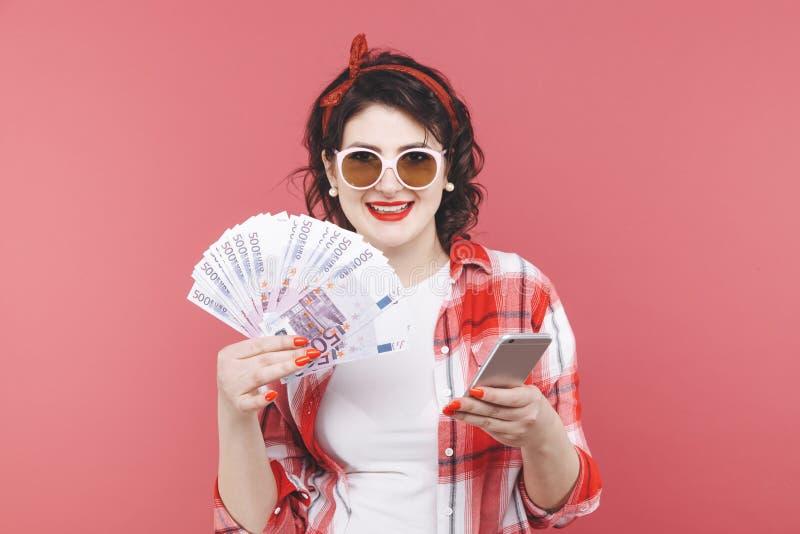 Stående av en le flicka som rymmer gruppen av pengarsedlar och ser mobiltelefonen som isoleras över rosa färger royaltyfri bild
