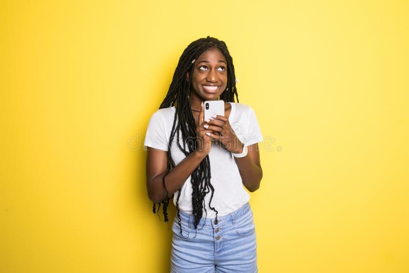 Stående av en le härlig afrikansk kvinna med den afro frisyren som rymmer mobiltelefonanseende över gul bakgrund royaltyfri fotografi
