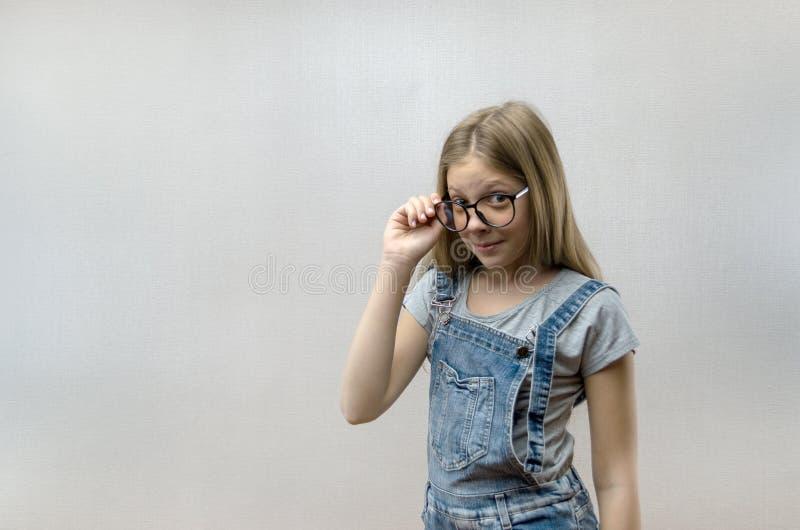 St?ende av en le h?rlig ung flicka med exponeringsglas smart barn nerdy arkivbilder