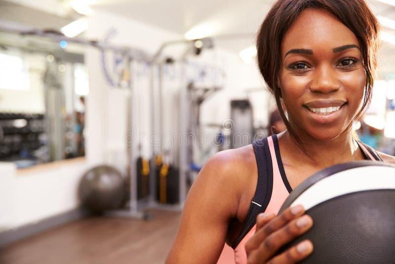 Stående av en le kvinna som rymmer en medicinboll på en idrottshall, kopieringsutrymme arkivbilder