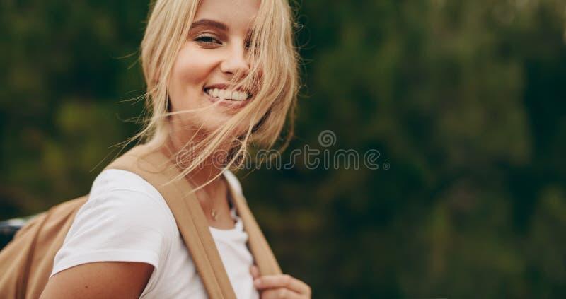 Stående av en le kvinnautforskare som bär en ryggsäck royaltyfria foton