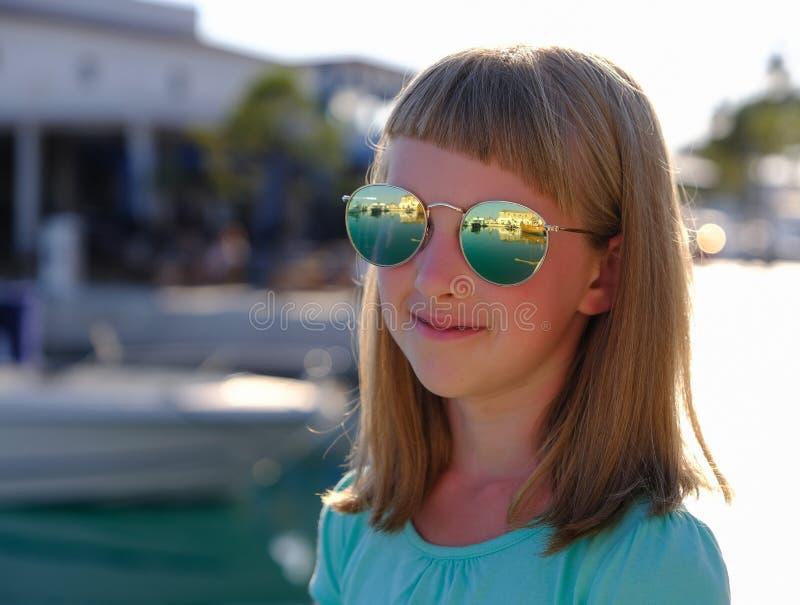 Stående av en le liten flicka i solexponeringsglas fotografering för bildbyråer