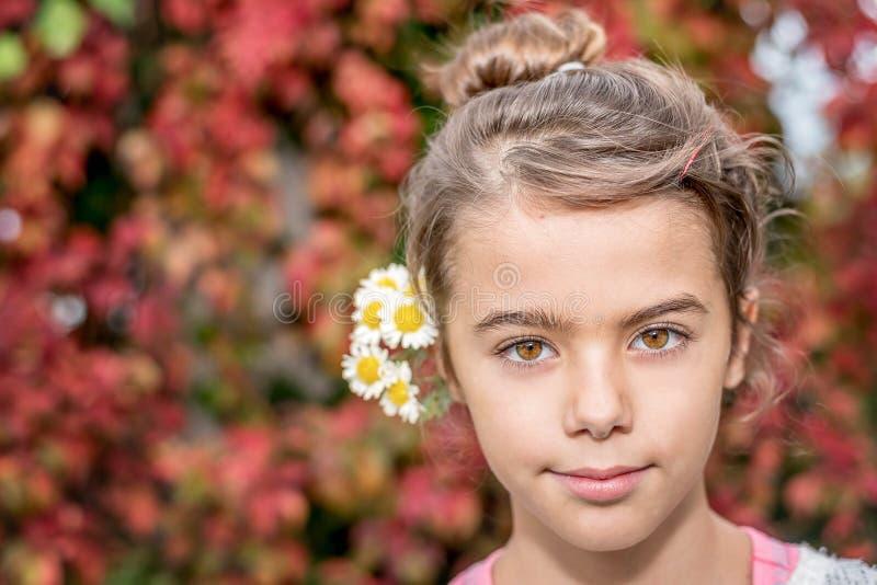 Stående av en le liten flicka med bakgrund för höstsidor royaltyfri bild