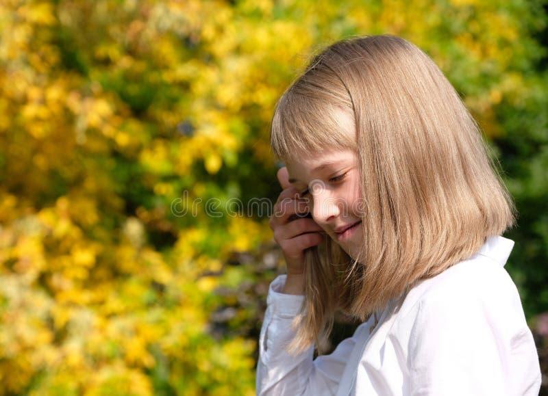 Stående av en le liten flicka på en höstbakgrund royaltyfria bilder