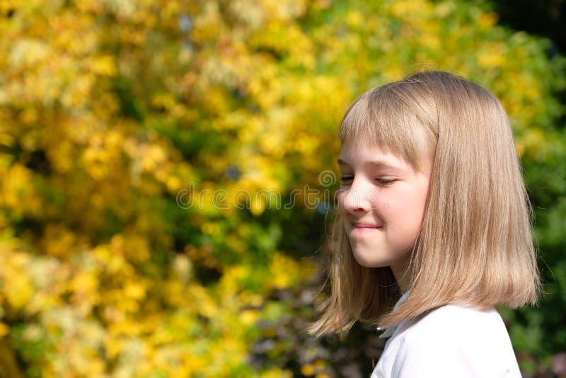 Stående av en le liten flicka på en höstbakgrund arkivfoto