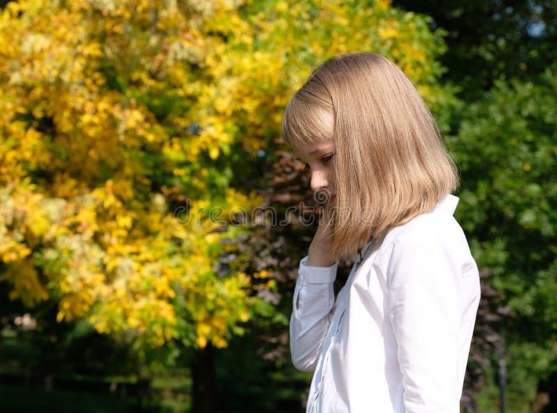 Stående av en le liten flicka på en höstbakgrund royaltyfria foton