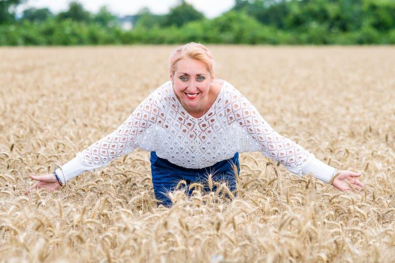 Stående av en le lycklig kvinna i ett moget vetefält royaltyfri fotografi