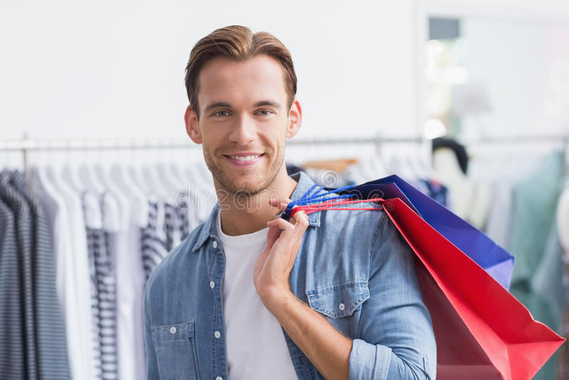 Stående av en le man med shoppingpåsar royaltyfri fotografi