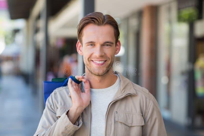 Stående av en le man med shoppingpåsar royaltyfri bild