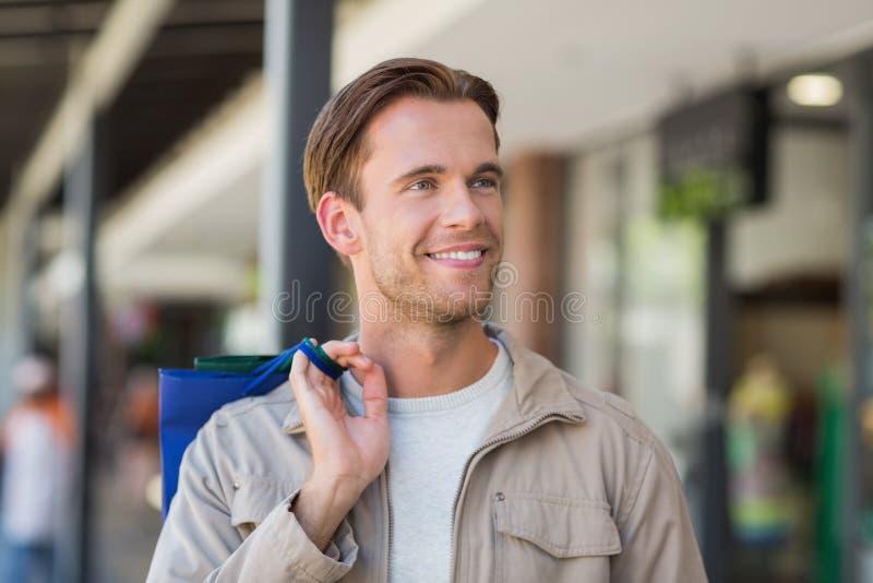 Stående av en le man med shoppingpåsar fotografering för bildbyråer