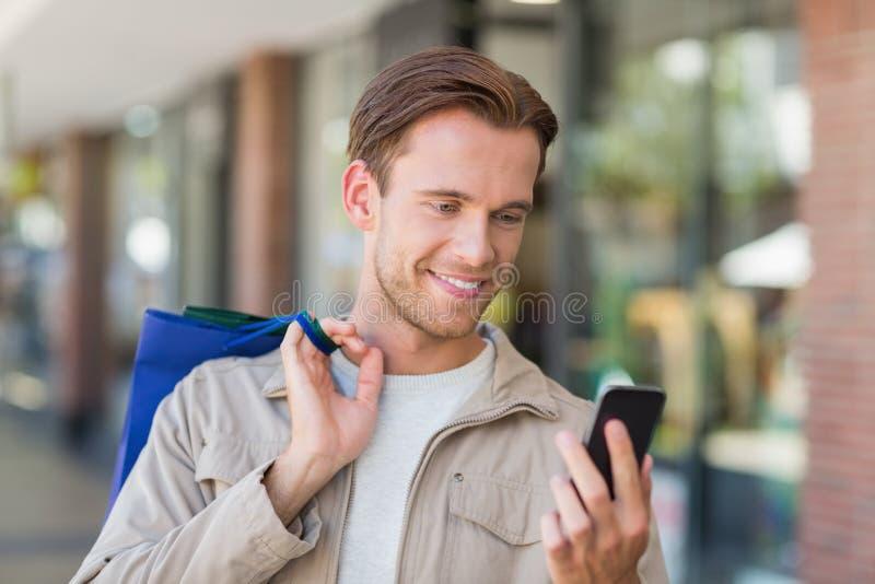 Stående av en le man som använder hans telefon arkivbild