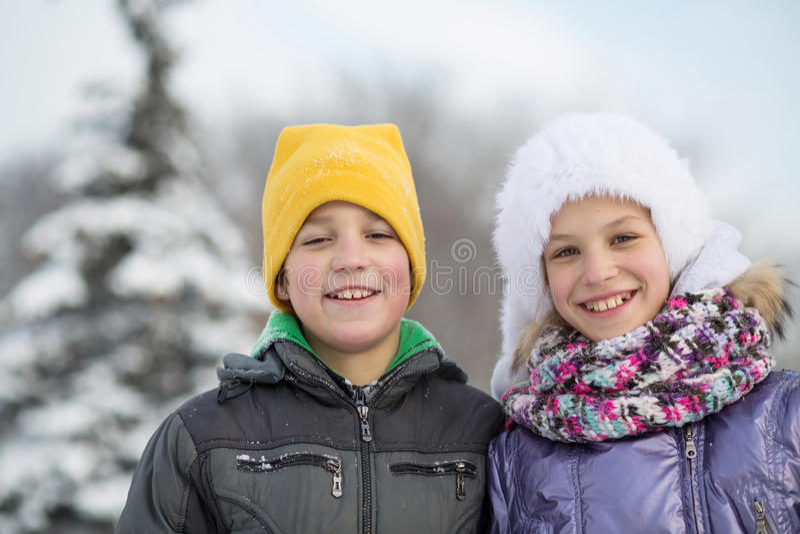 Stående av en le pojke med en flicka i vinter royaltyfria foton