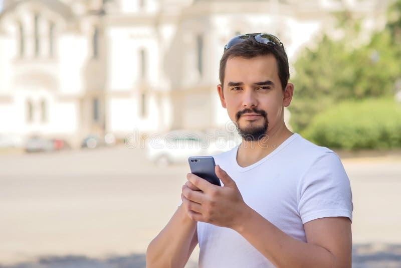 Stående av en le skäggig vuxen man med en smartphone på en stadsfyrkant i en solig vår- eller sommardag Turism och lopp arkivbilder