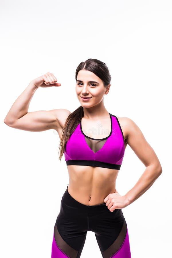 Stående av en le sportkvinna som böjer biceps och ser kameran som isoleras över vit bakgrund arkivfoton