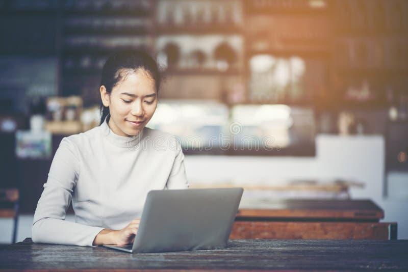 Stående av en le ung affärskvinna som arbetar på en bärbar datorwh royaltyfria foton