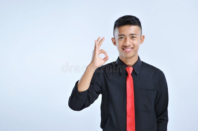 Stående av en le ung affärsman som visar det ok tecknet royaltyfri bild
