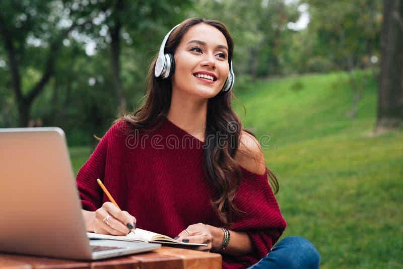 Stående av en le ung asiatisk flicka i hörlurar royaltyfria bilder