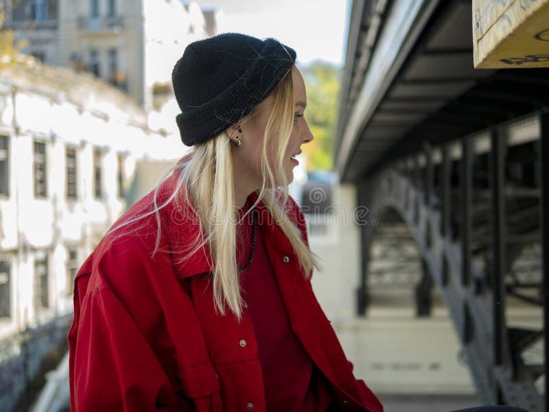 Stående av en le ung attraktiv flicka i ett rött omslag och stuckit svart omslag under bron arkivfoto