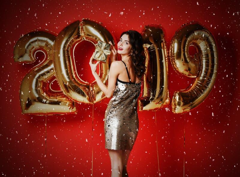 Stående av en le ung förvånad flicka i guld- skinande ask för klänningvisninggåva och att se kameran arkivfoto