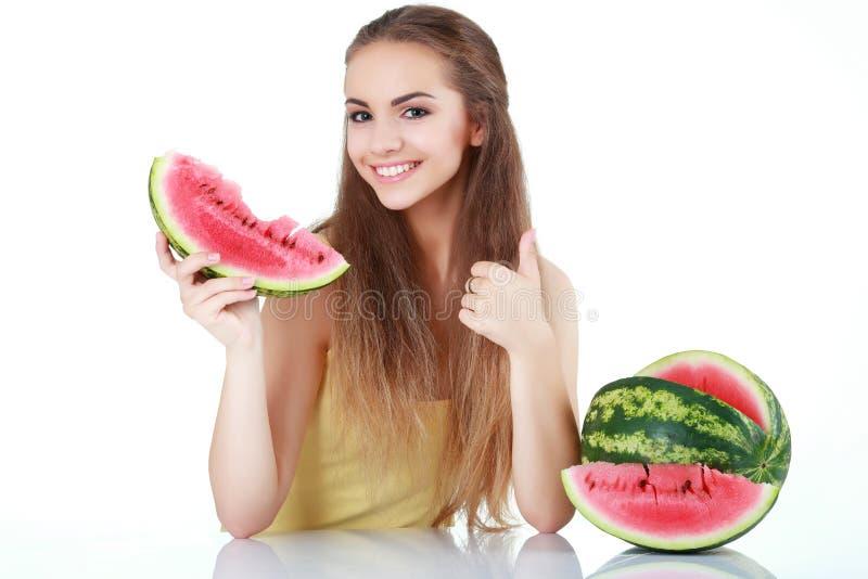 Stående av en le ung kvinna med vattenmelon som isoleras på wh royaltyfria bilder