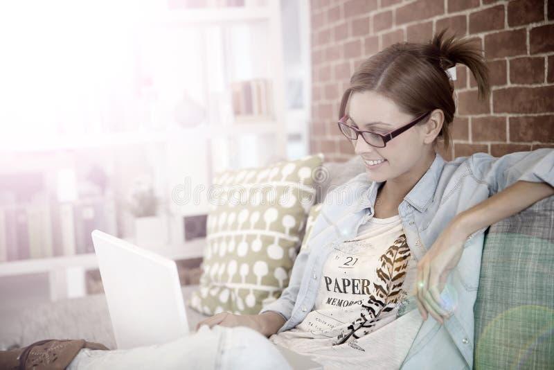 Stående av en le ung kvinna på en bärbar dator arkivbilder