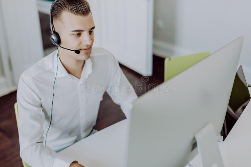 Stående av en le ung stilig man i formalwear med hörlurar med mikrofon genom att använda datoren i ett kontor royaltyfri bild