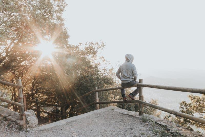 Stående av en ledsen eller olycklig man som sitter på en räcke på solnedgången arkivbild