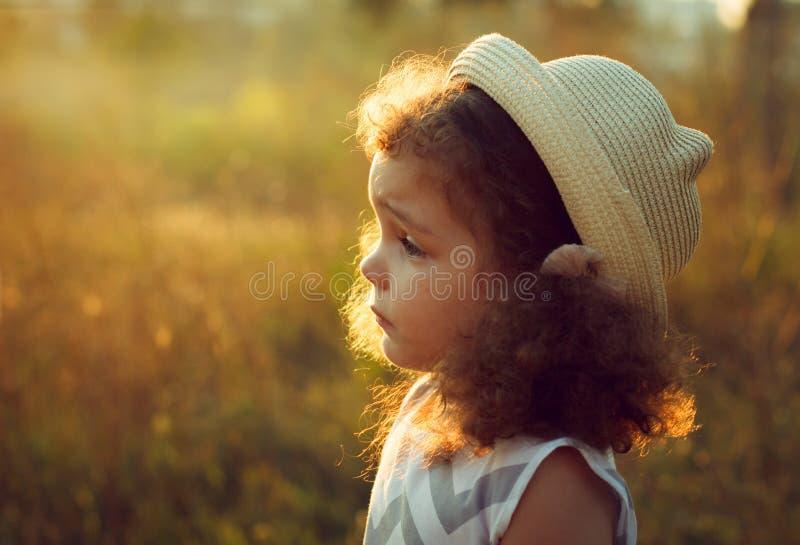 Stående av en ledsen lockig liten flicka i hösttid Solen är glänsande varmt aftonljus kopiera avstånd royaltyfri bild