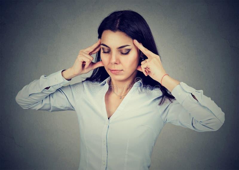 Stående av en ledsen ung kvinna med det bekymrade stressade framsidauttryckt som har huvudvärk arkivfoton