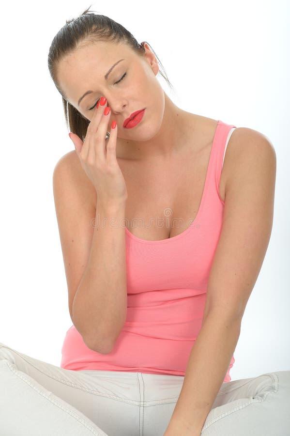 Stående av en ledsen ung kvinna som torkar en reva från hennes öga royaltyfri bild