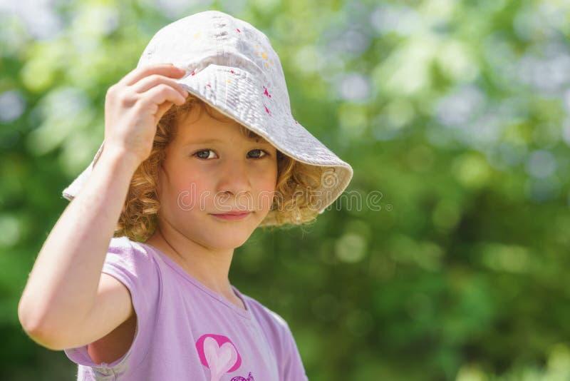 Stående av en liten caucasian flicka med en hatt som skyddar från den hårda solen Gr?n blurbakgrund arkivbilder