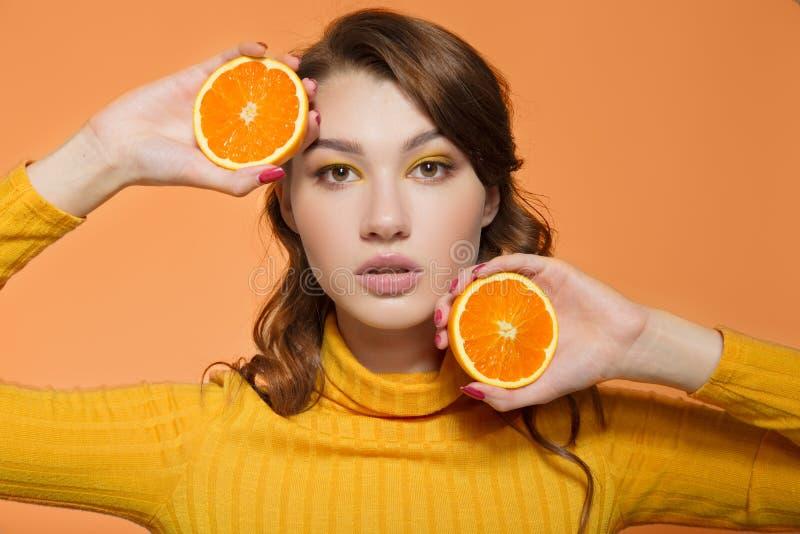 Stående av en ljus positiv ung kvinna med apelsiner i hennes händer Orange bakgrund arkivbild