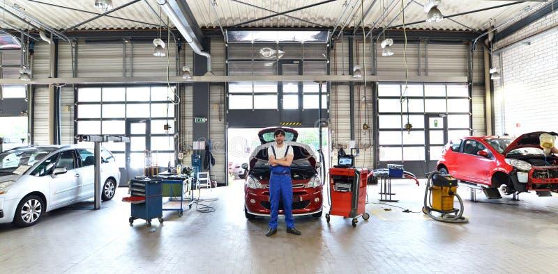 Stående av en lyckad mekaniker i ett garage - reparation och servi arkivbild