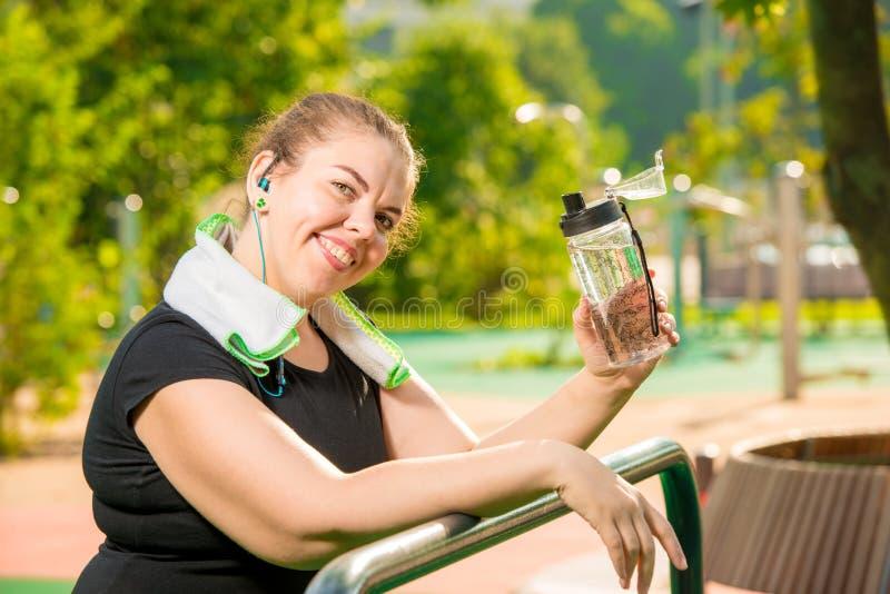Stående av en lycklig överdimensionerad kvinna med en flaska av vatten som ler, stående efter en genomkörare arkivbild