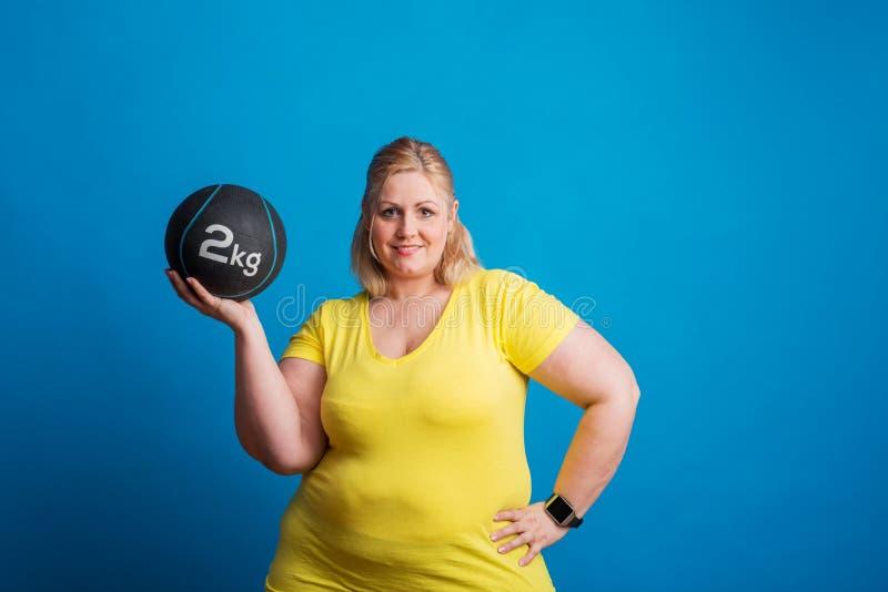 Stående av en lycklig överviktig kvinna som rymmer en tung boll i studio arkivfoto