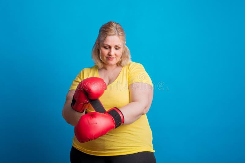 Stående av en lycklig överviktig kvinna som sätter på boxninghandskar i studio royaltyfri foto