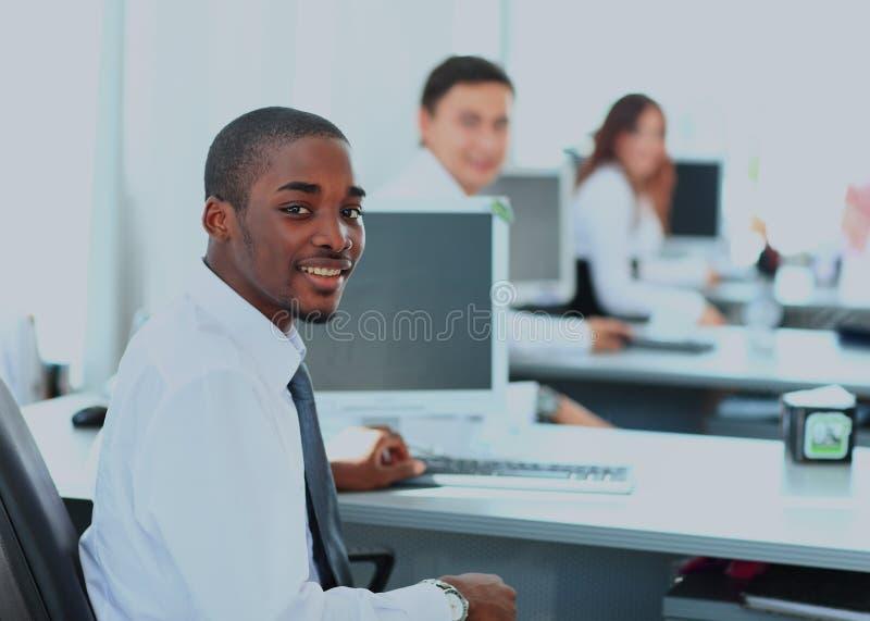 Stående av en lycklig afrikansk amerikanentreprenör som i regeringsställning visar datorbärbara datorn arkivbild