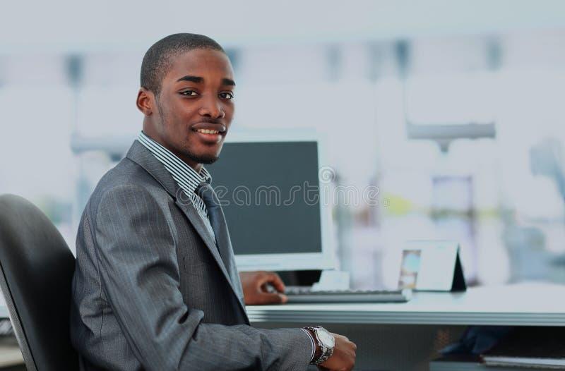 Stående av en lycklig afrikansk amerikanentreprenör som i regeringsställning visar datorbärbara datorn royaltyfri bild