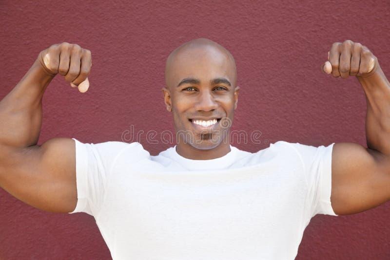 Stående av en lycklig afrikansk amerikanman som böjer muskler över kulör bakgrund royaltyfri fotografi