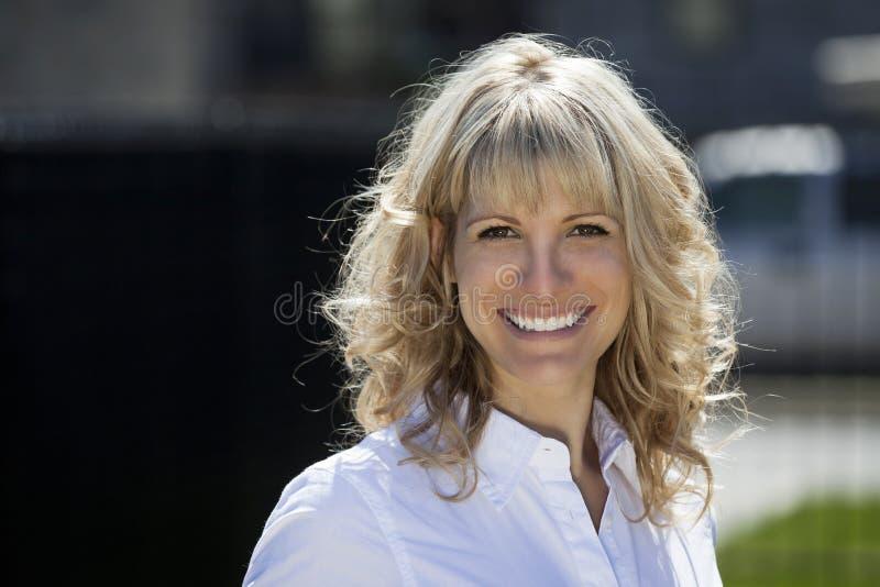 Stående av en lycklig blond kvinna utanför royaltyfri foto