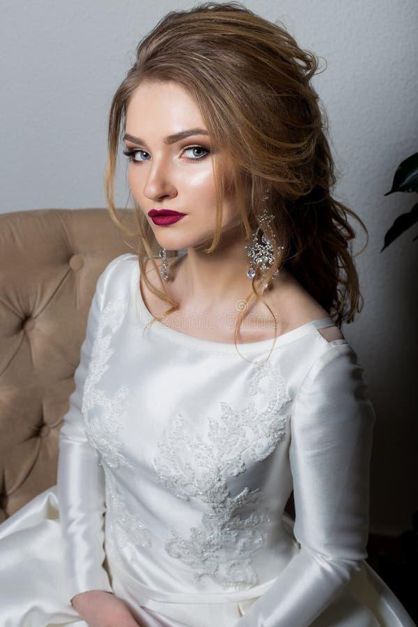 Stående av en lycklig brud för härlig sexig gullig flicka i en elegant klänning med ljus makeup i en vit klänning med ett ursnygg royaltyfri foto