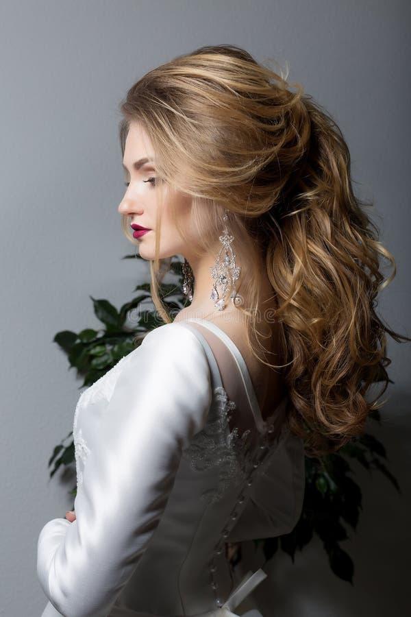 Stående av en lycklig brud för härlig sexig gullig flicka i en elegant klänning med ljus makeup i en vit klänning med ett ursnygg arkivbilder